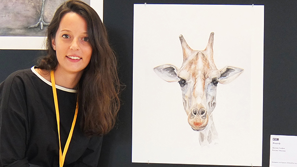 Shukhova stands beside one of her wildlife portraits. Photo courtesy of Sofiya Shukhova.