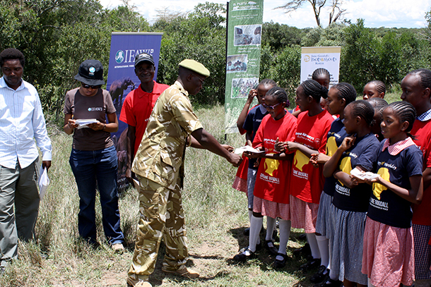 A Kenya Wildlife Service (KWS) officer serves students, from Ruaraka Academy, Nairobi, with cake celebrating Jane Goodall's birthday. IFAW supported Roots and Shoots to plant trees in celebration of Jane Goodall's 80th birthday.
