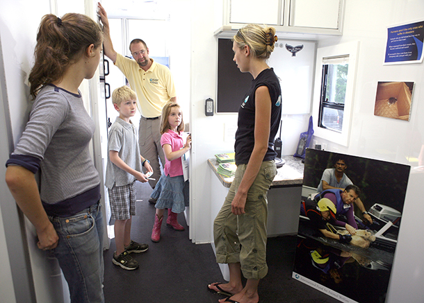 Young Jack and Emma Cady, center, with their dad, IFAW's AJ Cady, visit Jenn Miller, right, inside IFAW's Emergency response van, a mobile command center developed to better respond to disasters after Katrina.