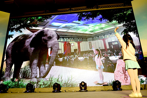 Two nine-year-old girls, Peng Minghui and Miao Yixin, interact with an elephant through the technological wizardry of augmented reality.