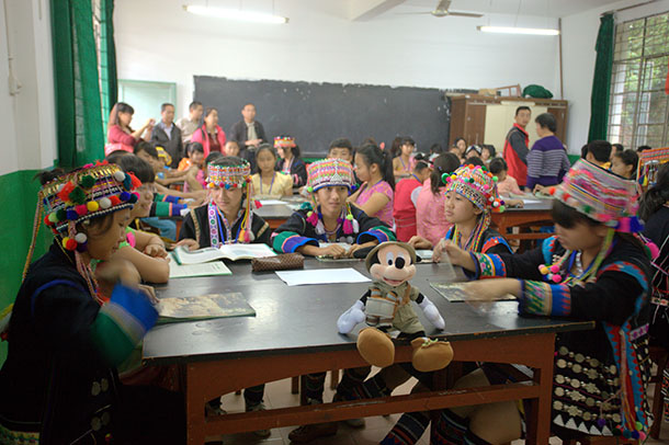 Yunnan children with a Mickey Mouse toy and elephant activity packs