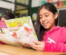 Girl in classroom reading Kind News